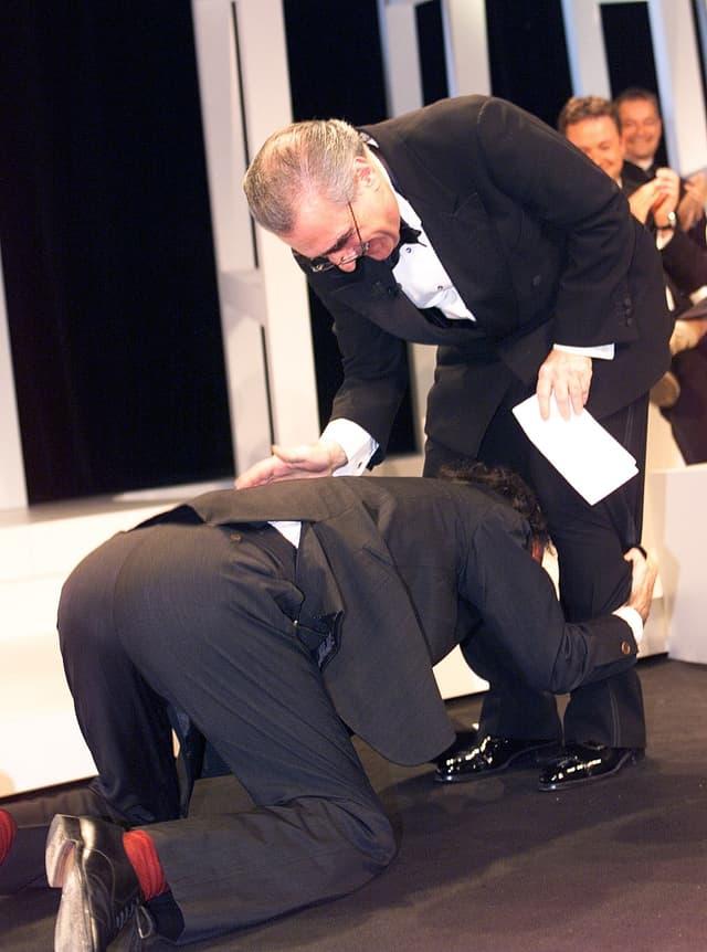 """Le réalisateur italien Roberto Benigni ne contient pas sa joie et baise même les pieds de Marin Scorsese, après avoir obtenu la Palme d'Or pour """"La Vie Est Belle"""" en 1998"""