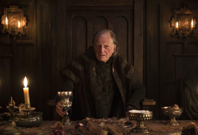 Walder Frey, assis à son siège qu'il ne semble jamais quitter dans Game of Thrones.