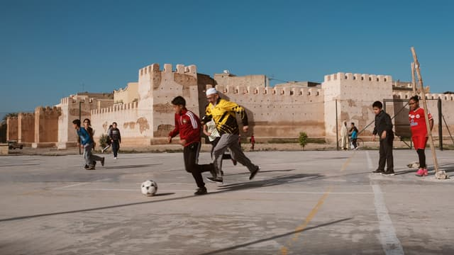 """Trois enfants jouant au football dans les rues de Chefchaouen, au Maroc. Une photo présente dans l'exposition """"Foot et Monde Arabe, la révolution du ballon rond"""", à l'Institut du Monde Arabe."""