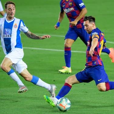 Lionel Messi face au défenseur de l'Espanyol Fernando Calero, lors d'un match de Liga au Camp Nou de Barcelone, le 8 juillet 2020.