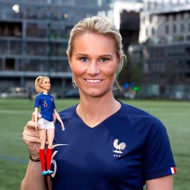 Amandine Henry pose avec sa poupée Barbie, à Londres, le 4 mars 2020.